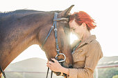 Young farmer woman hugging her horse - Concept about love between people and animals - Focus on girl eye