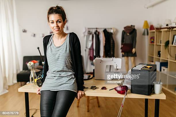 Young fashion designer in her studio, leaning against desk