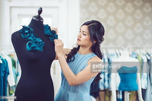 Young fashion designer is working in her showroom