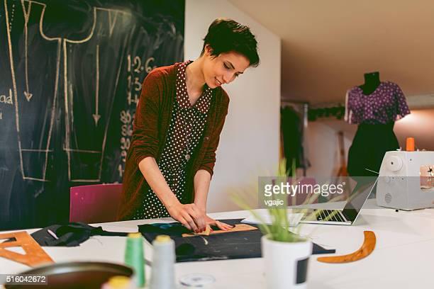 若いファッション・デザイナー彼女のワークショップで働く