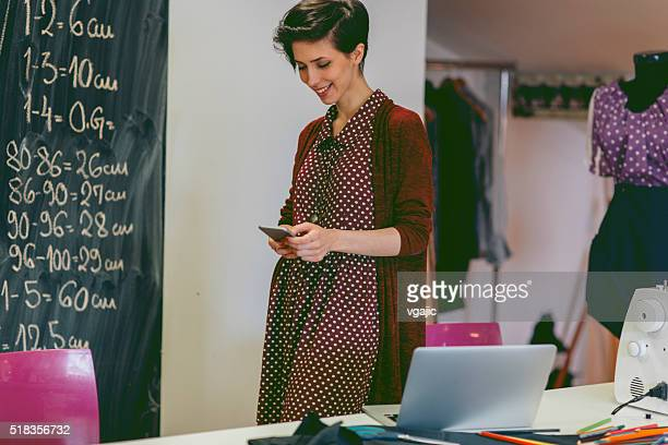Jovem Designer de de moda usando smartphone na sua oficina