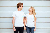 Young fashion stylish couple in white T-shirts stand on streets of the city in summertime.