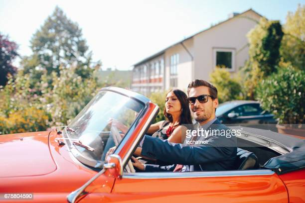 Young fashionable couple in an oldtimer convertible sportscar