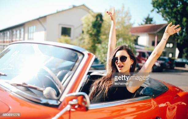 Young fashionable girl driving an oldtimer convertible sportscar