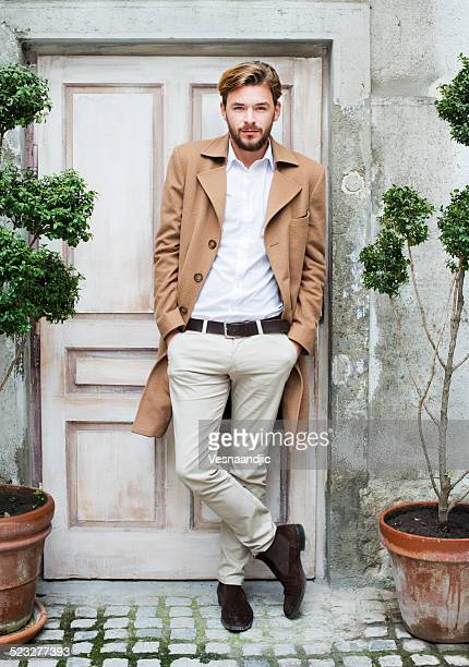 Young fashionable man standing in front of old door