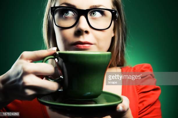 Alla moda giovane donna in occhiali beve una bevanda calda