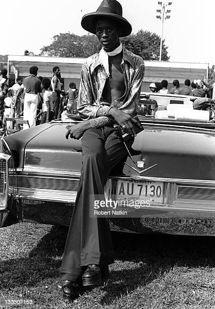 A young fashionably dressed African American man leans on the trunk of a Cadillac convertible while enjoying a day outdoors in a Chicago park 1973 He...