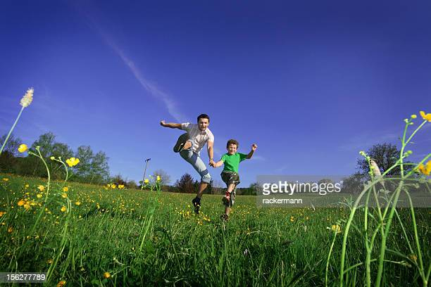 young father and boy jumping on meadow