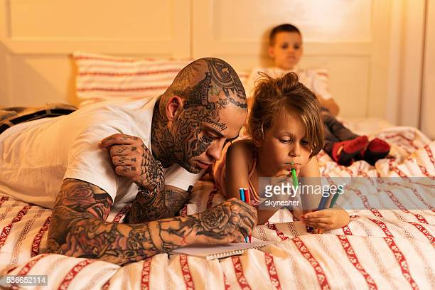 Young father and his daughter drawing in the bedroom.
