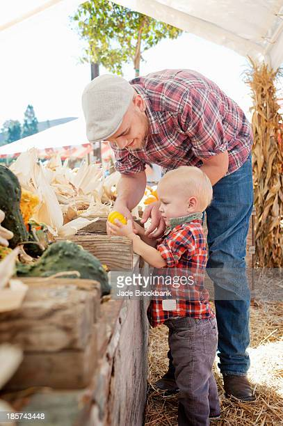 Young father and son looking at squashes