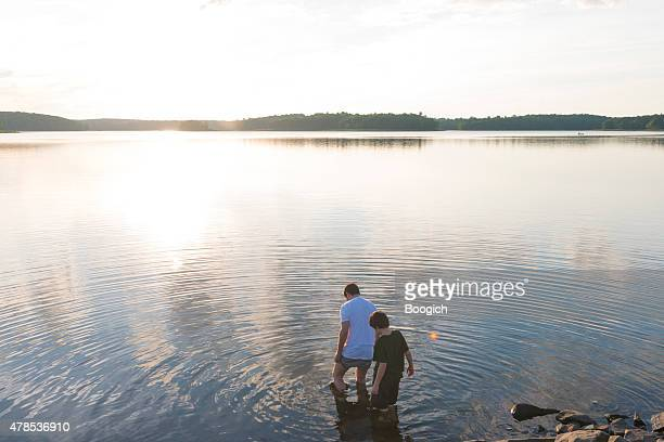 Young Father and Son Wading into Lake at Summer Sunset