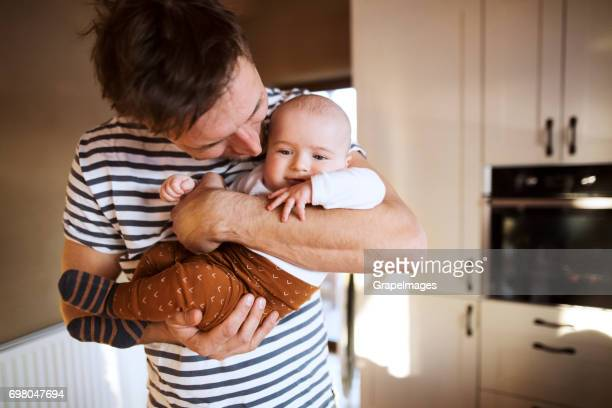Jeune papa à la maison dans la cuisine, tenant son fils dans les bras