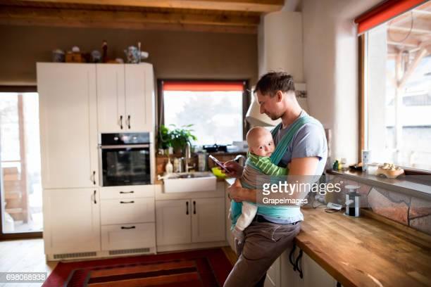 Jonge vader thuis in de keuken houden van slimme telefoon, SMS, zoontje in sling