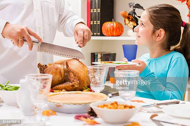 Young father carving thanksgiving turkey for his family