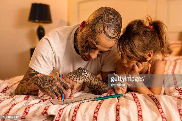 Young father drawing with his daughter in bedroom.