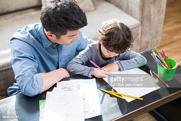 Young father helping son with homework