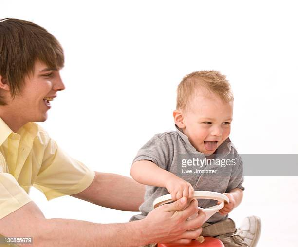 Young father playing with his son on the Bobbycar