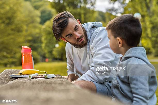 Young father talking to his small son in the park.