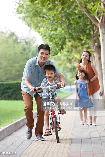 Young father teaching his son to ride a bicycle