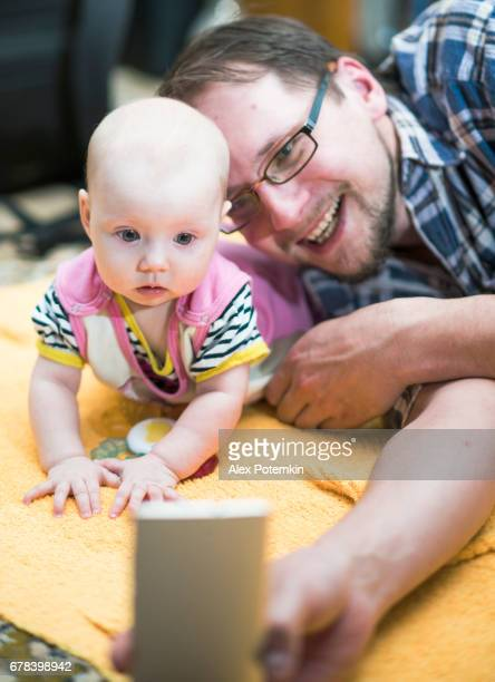 Young father with his baby daughter lying together on the floor and make selfie and have some video-conversation via the cellphone