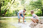 Young father with little boy playing with paper boats at river bank, sunny spring day.