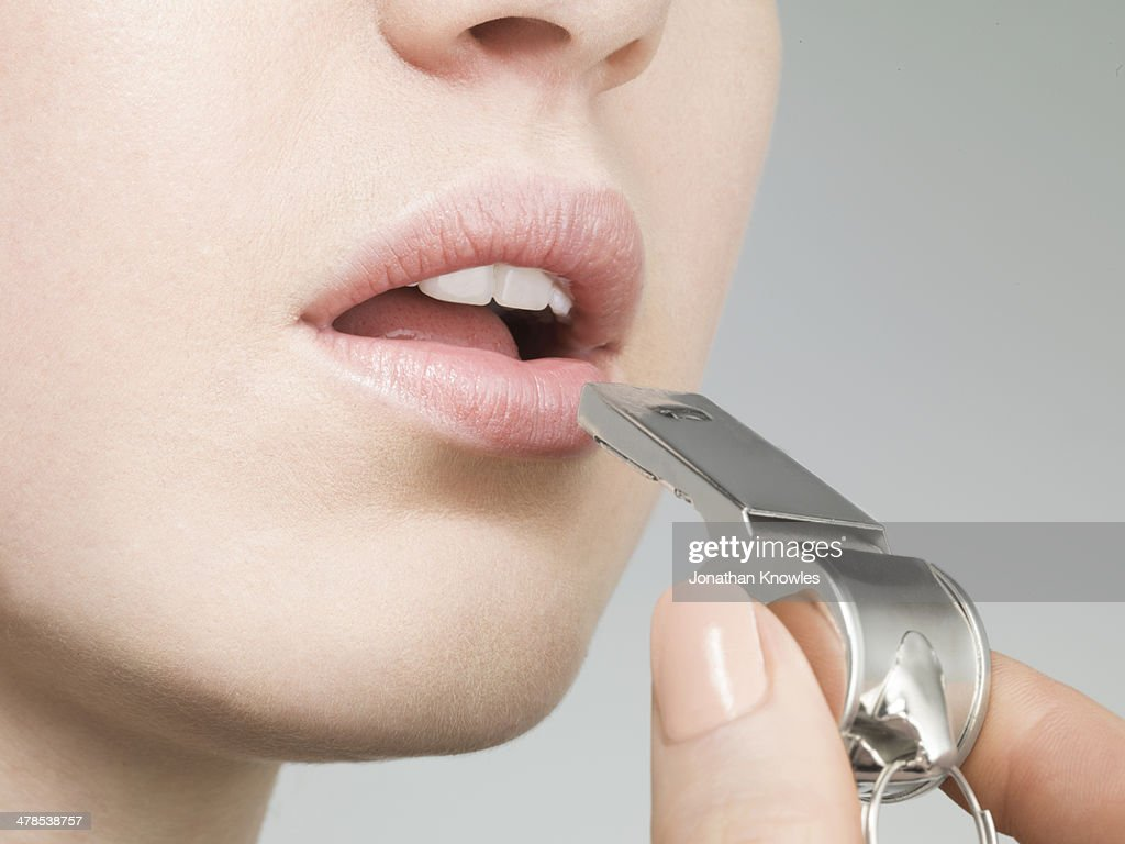 Young female about to blow a whistle : Stock Photo