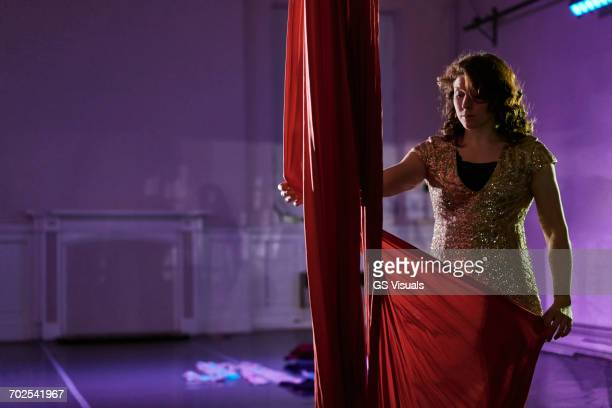 Young female acrobat preparing red silk rope