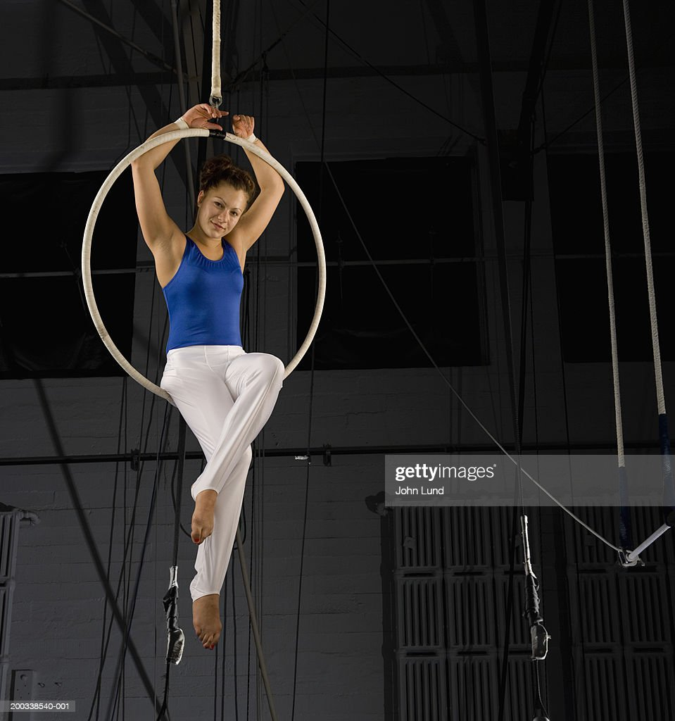 Young female aerialist sitting on ring