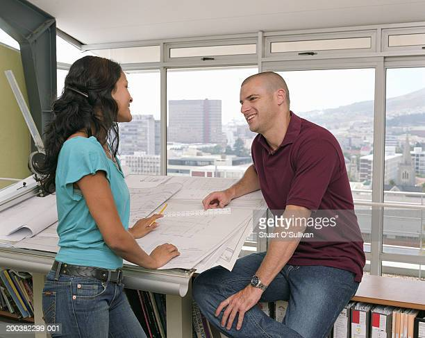 Young female and male  architects with plans in office, smiling