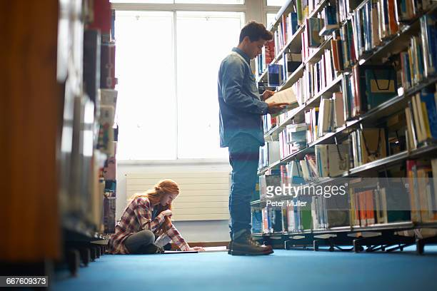 Young female and male college students working in library