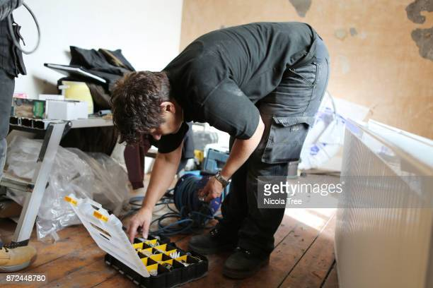 Young female apprentice plumber being taught by a female plumber how to fit a radiator on a wall.
