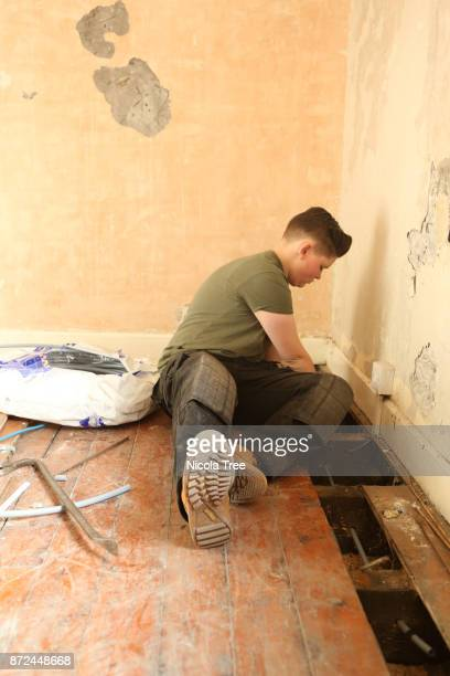 Young female apprentice plumber fitting new pipes for heating in an old house.