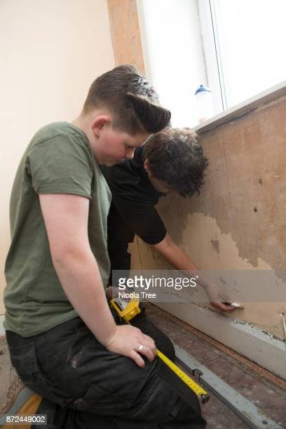 Young female apprentice plumber, measuring and marking a wall before fitting a radiator to it.