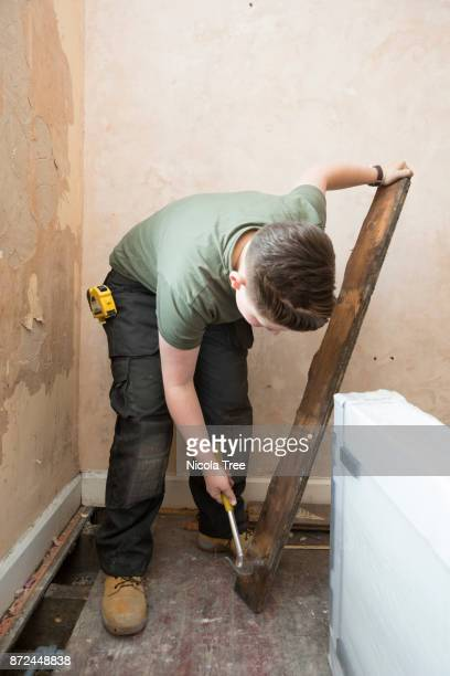 Young female apprentice plumber taking nails out of an old floorboard.