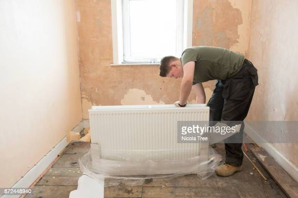 Young female apprentice plumber unpacking a new radiator before fitting it on the wall in an old house.