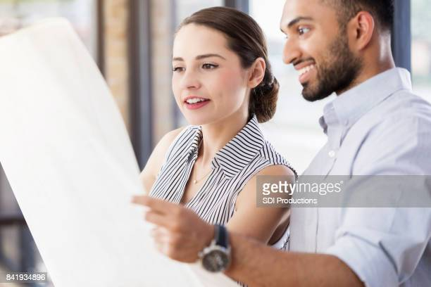 Young female architect studies blueprint with coworker