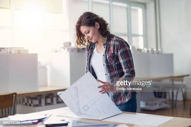 Young female architect working at a drawing board