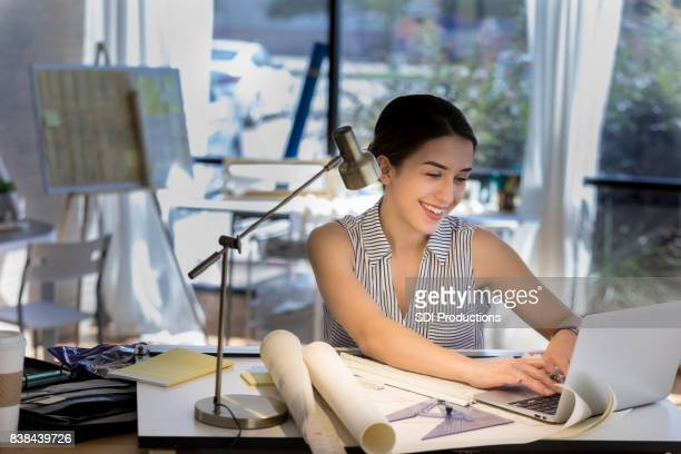 Young female architect works on computer
