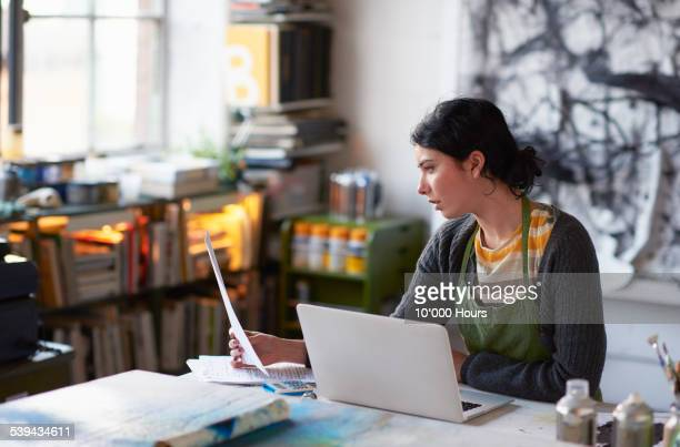 Young female artist in studio working on laptop
