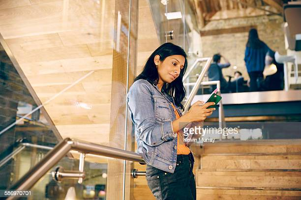 A young, female, Asian professional checks phone
