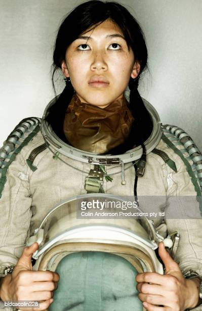 Young female astronaut looking up holding a space helmet