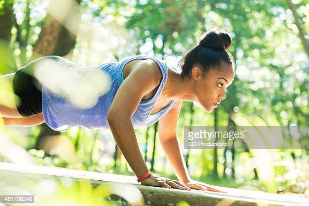 Young female athlete doing push-ups during outdoor workout