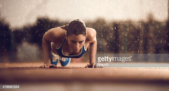 Young female athlete doing push-ups on a rain.
