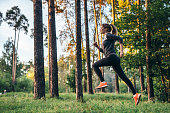 Young female athlete jogging in forest. Jogger doing morning physical training