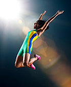 Young female athlete jumping mid air in celebration in stadium