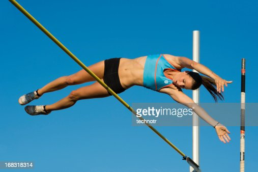Young female athlete jumping over the lath