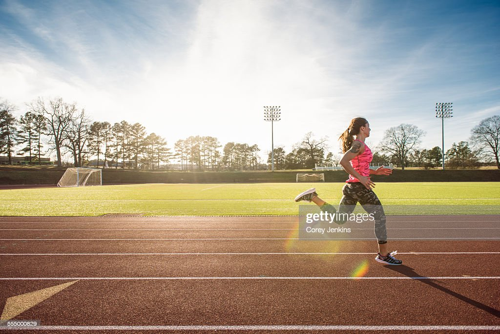 Young female athlete running on race track : Foto stock