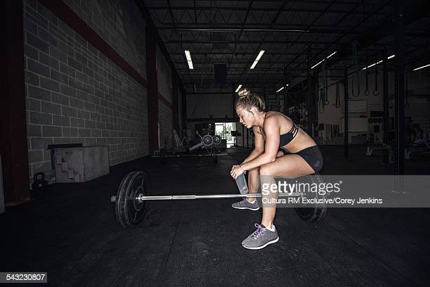 Young female athlete sitting on bar bell having a water break in gym