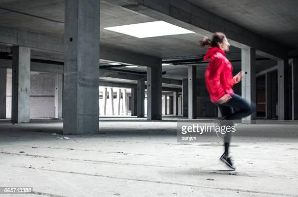 Young Female Athlete Skipping and Running Inside a Abandoned Building