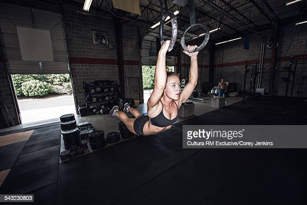 Young female athlete training on gym rings in gym